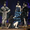 A model reaches to ask for help after a fall on the runway while displaying a creation by AsahiKasei Zhang Yichao collection during China Fashion Week in Beijing, Monday, March 29, 2010